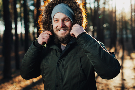 close up portrait of a bearded hipster tourist in gray hood man in the sunlight. Nature travel tourist