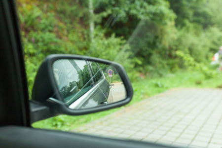 Landscape in the sideview mirror of a car , on road countryside