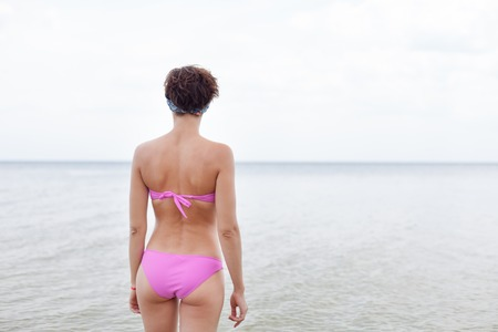 Rear view of young woman in bikini running on the beach. Caucasian female model on the sea shore