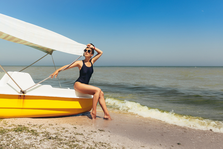 Young fashion woman relax on the beach. Happy island lifestyle. Active summer vacation concept