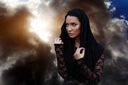A woman is a prophet sorcerer and a preacher in a black mystical cloak with a hood against a dramatic background