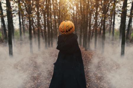 Portrait of a scary Jack-lantern with a pumpkin on his head. Halloween legend. Dressed in black coat. Autumn forest Foto de archivo