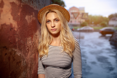 A beautiful young blond female student in a straw hat and a striped blouse is standing alone on the street. The concept of loneliness and sadness. Фото со стока