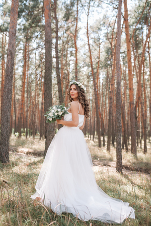 A cute curly woman in a white wedding dress with a wedding bouquet and wreath in her hair standing back to the camera in nature. Concept escaped bride. Forward to a happy bright future Runaway. Stock Photo