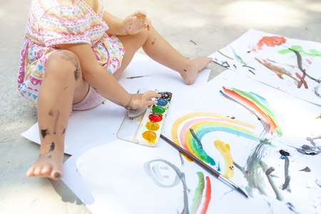 A little girl with curly hair sits on the floor and paints brightly colored paints on a large white sheet of paper. Summer vacation. Leisure for kids.
