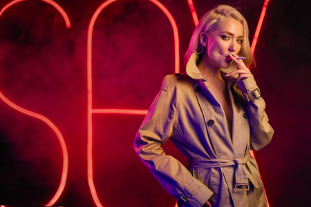 Young blondie sexy woman smoking a cigarette, wearing the beige coat and having a bright makeup. Red neon smoky background Stockfoto