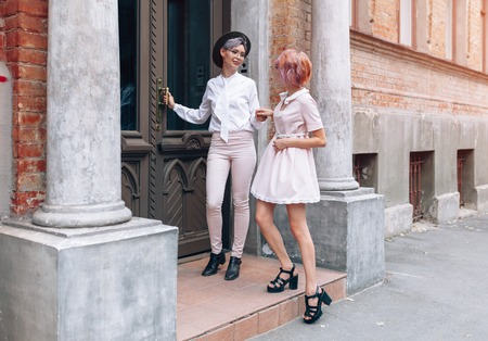 Stylish lesbian couple holding hands near the old building in the city