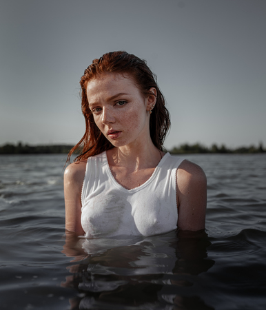 Young pretty red-haired woman in the white shirt standing in the water with gloomy face