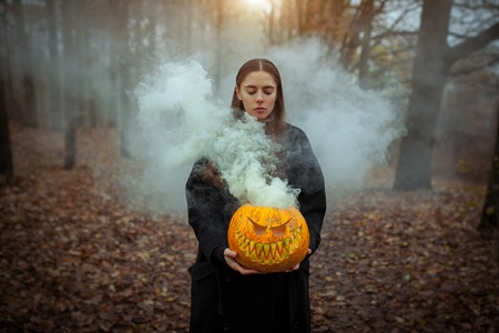 Young woman in the black coat holding the halloween pumpkin with the smoke coming from inside of it in the autumn forest