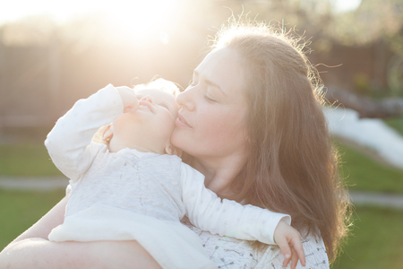 Mother holding her little daughter on her shoulder in the sun rays