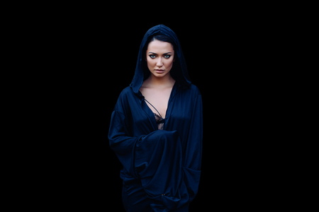 Young beautiful mysterious woman with a black hair and in the dark blue cloak with hood at the black background