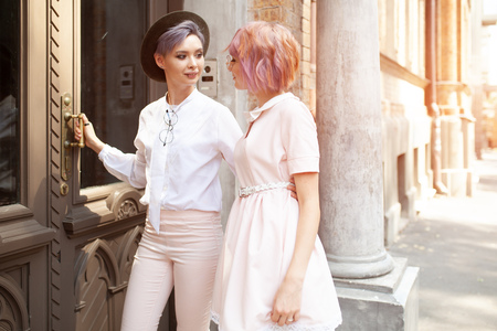 Stylish lesbian couple entering the building in the city Фото со стока
