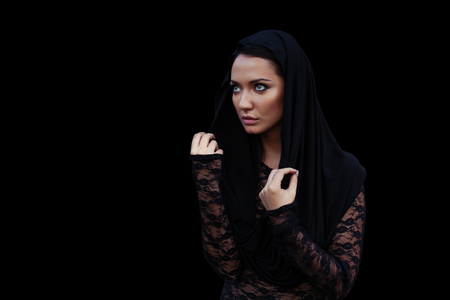Young beautiful mysterious woman with a black hair and in the black hood and blouse at the black backgtound Zdjęcie Seryjne