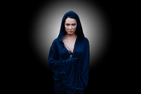 Young beautiful mysterious woman with a black hair and in the dark blue cloak with hood at the black background with white lighting