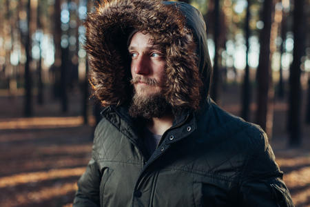 Portrait, close-up of young stylishly serious man with a beard dressed in rgreen winter jacket with a hood and fur on his head stands against the background of pine forest Stockfoto