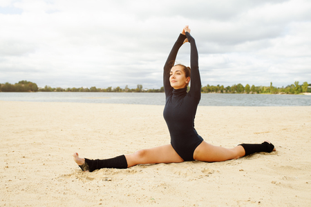 Beautiful middle-aged girl doing yoga exercises on the shore of a beautiful lake on a sunny autumn day. Sports outdoor recreation concept with free space for text