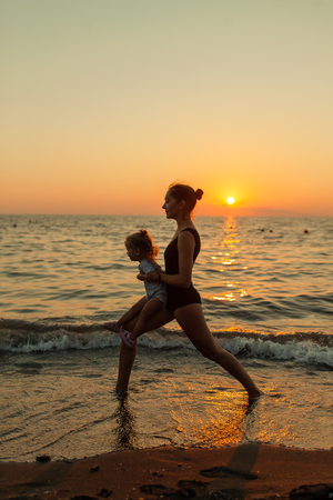 woman and girl silhouette practicing balancing yoga warrior pose together during ocean sunset with bright orange sky and water reflections. 写真素材