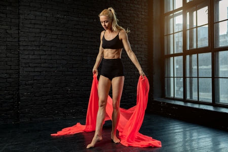 Young blonde ballerina in sportswear underwear dances and jumps in a studio with black brick on the background. modern ballet performance. Perfect fitness woman body. Фото со стока