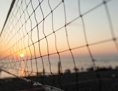 Blick auf den Sonnenaufgang durch das Volleyballnetz. Früher Morgen, dramatischer Sonnenaufgang über dem Meerwasser.