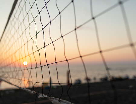View of the sunrise through the volleyball net. Early morning , dramatic sunrise over sea water. 免版税图像