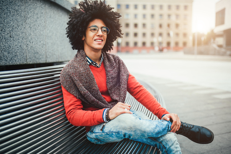 A handsome young Egyptian curly guy sitting on a bench dressed in a bright orange sweater and jeans. Happy people. The student walks in the break between the lessons Imagens