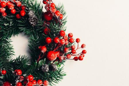 Ghirlanda decorativa di Natale di agrifoglio, edera, vischio, cedro e rametti di foglie di leyland con bacche rosse su sfondo bianco