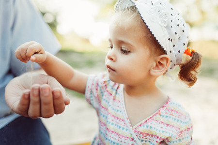 A little girl pours sand into her unrecognizable fathers hand. The concept of the transience of time and the fact that new generations replace the old. Stock Photo