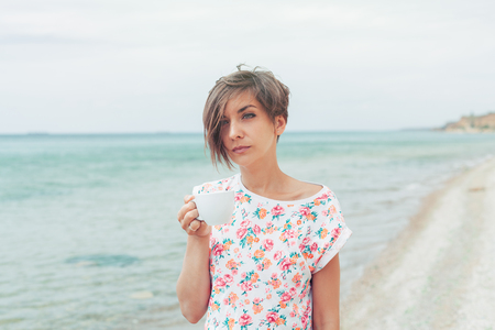 Beautiful woman with short haircut relax during exotic vacation on the beach enjoying sweet coffee or tea 写真素材