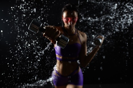 Beautiful caucasian sportswoman posing with dumbbells on a black background in spray of water. Over power concept for poster or banner Reklamní fotografie