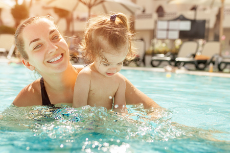 Mom and little daughter are played in the open swimming pool. Family with one child on vacation in warm countries. Positive people on vacation. Summer leisure