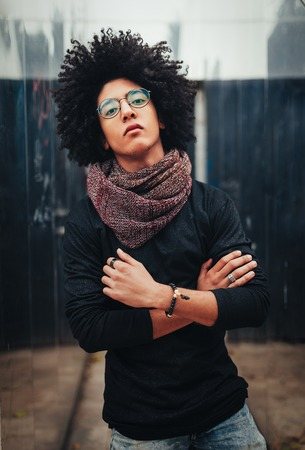 Young Afro american young businessman or student wearing black turtleneck sweater and scarf and having curly dark hair. Concept of stylish and fashionable look posing outdoor