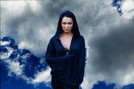 Young beautiful mysterious woman with black hair and in the dark blue cloak with hood at the sky background with clouds