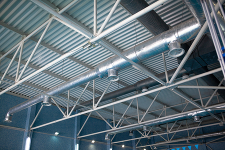 Ventilation system on the ceiling of large buildings. Ventilation pipes in silver insulation material hanging from the ceiling inside new building