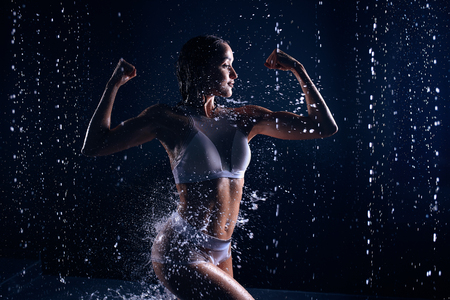 Beautiful athletic caucasian girl with a perfect figure is standing under the water. Fitness woman in a spray of water. Sports freshness. concept