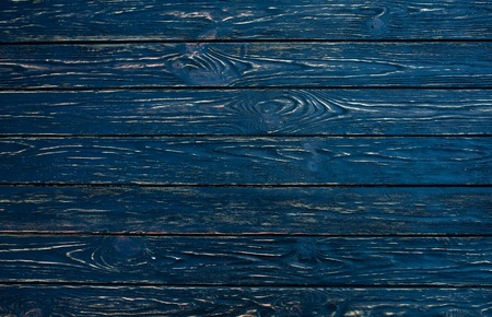 Dark black wood texture background viewed from above. The wooden planks are stacked horizontally and have a worn look. This surface would be great as design element for a wall, floor, table