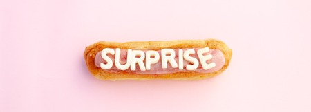 Surprise word written in eclair voluminous white letters on a beautiful pink background. greting card Фото со стока