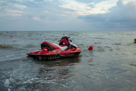 Ureki, Georgia August 2018 Black Sand Beach Red Hydrocycle on the sea water at the bad weather before storm Éditoriale