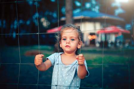 the little girl holds on to the fence with both hands and looks into the camera through the grid.