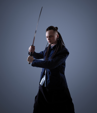 Young man dressed in the white shirt and dark blue jacket with dreadlocks holding a samurai sword. Glamour photo. Studio shooting. business man with Japanes sword