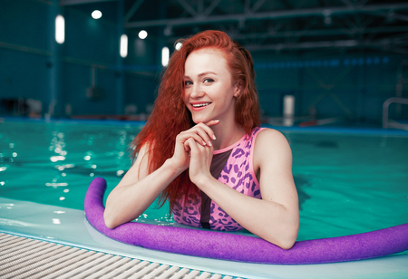A beautiful young red-haired girl in a fashionable swimsuit in the style of the 80s stands with a noodles in her hands in an indoor swimming pool. Physio therapy and alternative sport. trainer