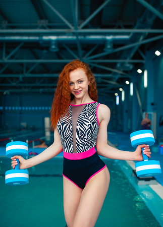 A beautiful young red-haired girl in a fashionable swimsuit in the style of the 80s stands with a ball in her hands in an indoor swimming pool. Physio therapy and alternative sport. trainer 版權商用圖片