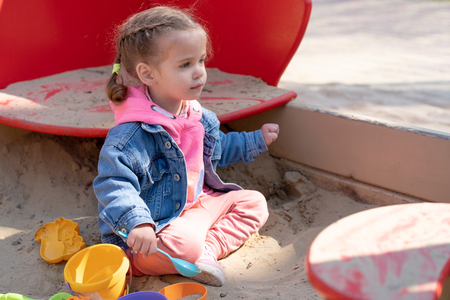 Cute little caucasian girl on the playground, happy child with pleasure spending time outdoors, happy carefree childhood Summer season childrens leisure