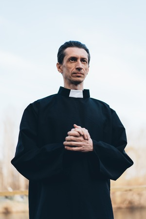 Portrait of handsome catholic priest or pastor with collar Standing outdoors