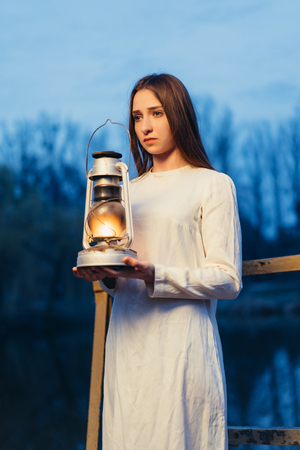 Mysterious mystical girl in a dark night forest with a kerosene lamp in her hands Halloween concept
