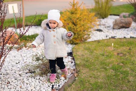 Little Caucasian girl walks in autumn park. autumn childrens wear collection