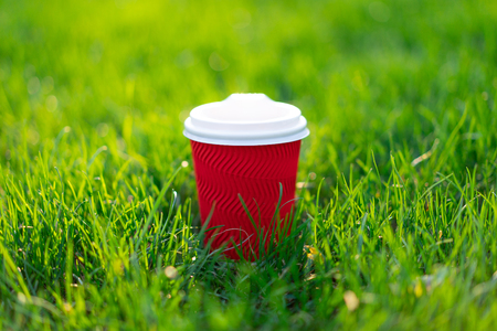 A red disposable cardboard cup with hot tea stands in fresh green grass. morning fresh concept Reklamní fotografie