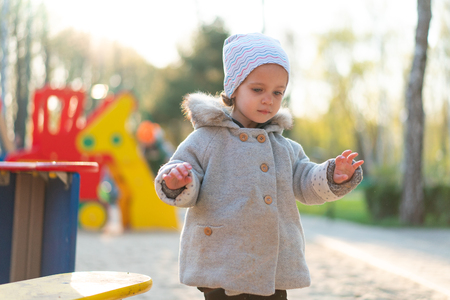 little cute girl playing at the playground in autumn Dressed in the gray fashionable coat