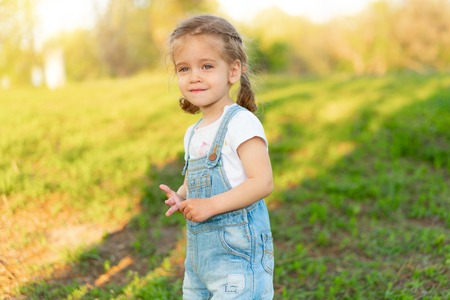 Summer season. Little Caucasian girl walks on nature dressed in denim overalls. Children's fashion. childhood