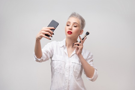 Studio portrait of beautiful trendy girl with short hair taking selfie via cell phone over white isolated