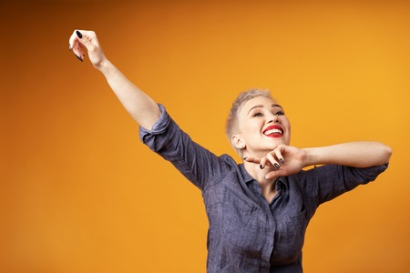 Portrait of young girl with blond short hairstyle looking at camera and laugh showing swag dab on orange background with copy space. Woman surprised and smiling. positive emotion